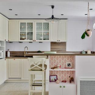 パリの小さいシャビーシック調のおしゃれなキッチン (アンダーカウンターシンク、ベージュのキャビネット、木材カウンター、茶色いキッチンパネル、木材のキッチンパネル、パネルと同色の調理設備、磁器タイルの床、ベージュの床、茶色いキッチンカウンター) の写真