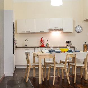 Cette image montre une cuisine ouverte design en L de taille moyenne avec des portes de placard blanches et aucun îlot.