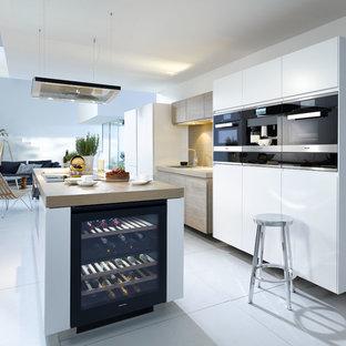 Immagine di una grande cucina contemporanea con ante bianche, top in legno, paraspruzzi marrone, elettrodomestici neri, pavimento con piastrelle in ceramica e isola