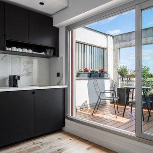 Exemple d'une petite cuisine linéaire tendance avec un évier posé, un placard à porte plane, des portes de placard noires, une crédence blanche, un sol en bois clair, aucun îlot, un sol beige et un plan de travail blanc.