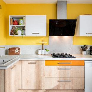 Cette image montre une cuisine design en L de taille moyenne avec un évier posé, un placard à porte plane, des portes de placard en bois clair, une crédence grise, une crédence en carreau de porcelaine, un électroménager encastrable et un plan de travail gris.