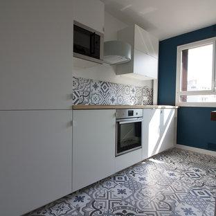 パリの中くらいの北欧スタイルのおしゃれなキッチン (白いキャビネット、木材カウンター、セメントタイルのキッチンパネル、セメントタイルの床、青い床) の写真