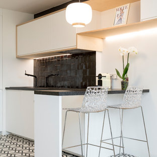 Small contemporary single-wall open plan kitchen in Paris with flat-panel cabinets, white cabinets, black splashback, a submerged sink, granite worktops, ceramic splashback, stainless steel appliances, cement flooring, no island, multi-coloured floors and black worktops.