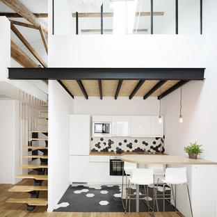 モンペリエの中くらいの北欧スタイルのおしゃれなキッチン (ドロップインシンク、白いキャビネット、木材カウンター、マルチカラーのキッチンパネル、セラミックタイルのキッチンパネル、白い調理設備、セラミックタイルの床、フラットパネル扉のキャビネット) の写真