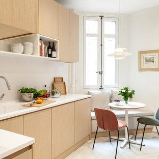 Idée de décoration pour une cuisine américaine design en L avec un évier intégré, un placard à porte plane, des portes de placard en bois clair, une crédence blanche et un sol beige.