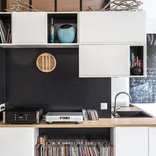 パリの中サイズのモダンスタイルのおしゃれなキッチン (木材カウンター、ドロップインシンク、フラットパネル扉のキャビネット、白いキャビネット、黒いキッチンパネル、スレートの床、黒い調理設備、クッションフロア、アイランドなし、グレーの床、ベージュのキッチンカウンター) の写真