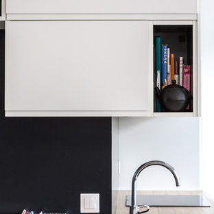 Design ideas for a mid-sized modern single-wall open plan kitchen in Paris with wood benchtops, a drop-in sink, flat-panel cabinets, white cabinets, black splashback, slate splashback, black appliances, vinyl floors, no island, grey floor and beige benchtop.