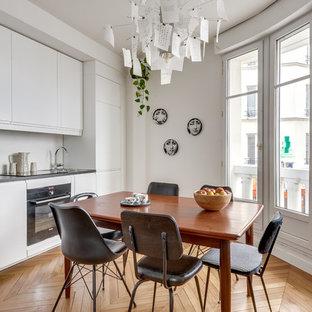 Cette photo montre une cuisine américaine linéaire scandinave avec un évier posé, un placard à porte plane, des portes de placard blanches, une crédence blanche, un électroménager noir, un sol en bois brun, aucun îlot, un sol marron et un plan de travail noir.