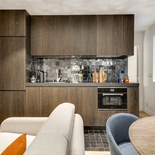 Photo of a mid-sized contemporary single-wall open plan kitchen in Paris with a single-bowl sink, dark wood cabinets, black splashback, terra-cotta splashback, panelled appliances, no island, beaded inset cabinets and terra-cotta floors.