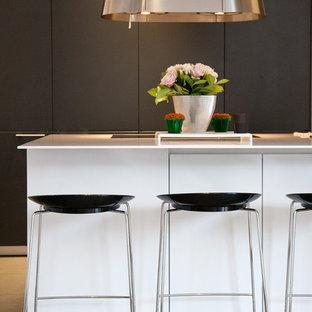 Aménagement d'une cuisine américaine parallèle contemporaine de taille moyenne avec un îlot central et des portes de placard noires.