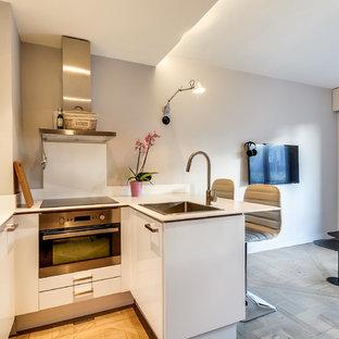 Inspiration pour une petite cuisine ouverte design en U avec un évier posé, un placard à porte plane, des portes de placard blanches, une crédence blanche, un électroménager en acier inoxydable, une péninsule et un sol en bois clair.