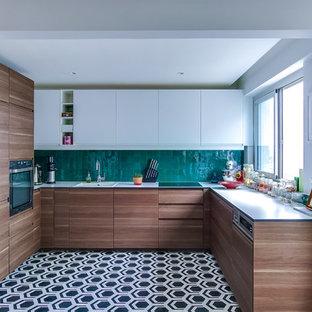 Offene Moderne Küche in U-Form mit Unterbauwaschbecken, Kassettenfronten, Küchenrückwand in Grün, Rückwand aus Terrakottafliesen, Küchengeräten aus Edelstahl, Zementfliesen, weißen Schränken und Laminat-Arbeitsplatte in Paris