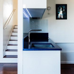 Идея дизайна: маленькая параллельная кухня-гостиная в современном стиле с одинарной раковиной, фасадами с декоративным кантом, белыми фасадами, столешницей из кварцита, белым фартуком, фартуком из стекла, техникой из нержавеющей стали, паркетным полом среднего тона, коричневым полом и синей столешницей без острова
