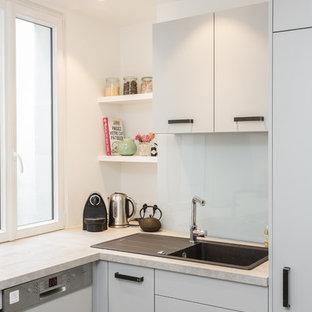 パリの中サイズのエクレクティックスタイルのおしゃれなキッチン (淡色無垢フローリング、アイランドなし、ベージュの床、ドロップインシンク、フラットパネル扉のキャビネット、グレーのキャビネット、ラミネートカウンター、白いキッチンパネル、ガラス板のキッチンパネル、シルバーの調理設備の、グレーのキッチンカウンター) の写真