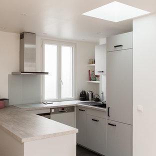 パリの中サイズのエクレクティックスタイルのおしゃれなキッチン (ドロップインシンク、フラットパネル扉のキャビネット、グレーのキャビネット、ラミネートカウンター、白いキッチンパネル、ガラス板のキッチンパネル、シルバーの調理設備の、セラミックタイルの床、グレーの床、グレーのキッチンカウンター) の写真