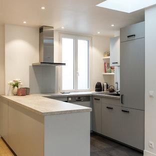 パリの中くらいのエクレクティックスタイルのおしゃれなキッチン (淡色無垢フローリング、アイランドなし、ベージュの床、ドロップインシンク、フラットパネル扉のキャビネット、グレーのキャビネット、ラミネートカウンター、白いキッチンパネル、ガラス板のキッチンパネル、シルバーの調理設備、グレーのキッチンカウンター) の写真