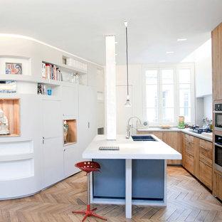 Inspiration pour une grande cuisine ouverte parallèle design avec des portes de placard en bois brun, un électroménager encastrable, un sol en bois brun et un îlot central.