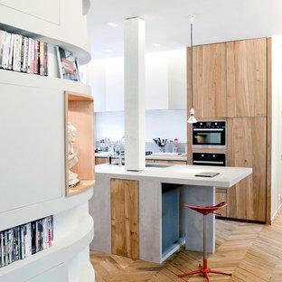 Aménagement d'une grande cuisine américaine contemporaine en L avec des portes de placard en bois brun, une crédence grise, un électroménager encastrable, un sol en bois brun et un îlot central.