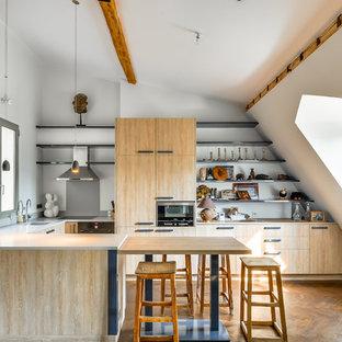 Cette photo montre une grande cuisine américaine éclectique en U avec un placard à porte plane, des portes de placard en bois clair, un sol en bois brun et une péninsule.