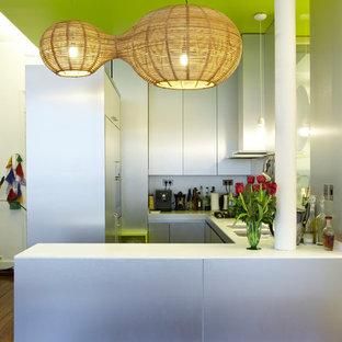 Idées déco pour une petite cuisine ouverte contemporaine en U avec un placard à porte plane, des portes de placard grises et une péninsule.