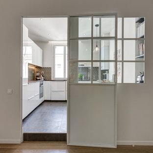 Inredning av ett skandinaviskt avskilt, mellanstort brun brunt l-kök, med brunt stänkskydd, cementgolv, grått golv, en nedsänkt diskho, släta luckor, vita skåp, laminatbänkskiva, stänkskydd i cementkakel, svarta vitvaror och en halv köksö
