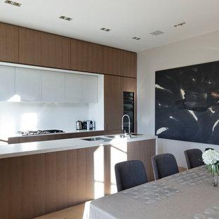 Exemple d'une grande cuisine américaine parallèle tendance avec un évier 2 bacs, une crédence blanche, un sol en bois clair, un îlot central et des portes de placard en bois sombre.