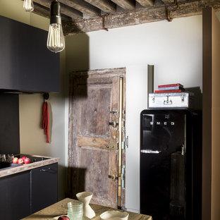 パリの中サイズのエクレクティックスタイルのおしゃれなキッチン (一体型シンク、木材カウンター、シルバーの調理設備の、テラコッタタイルの床、赤い床) の写真
