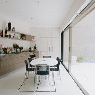 Inspiration pour une cuisine américaine design en L avec un évier encastré, un placard à porte plane, des portes de placard en bois brun, une crédence blanche, un électroménager en acier inoxydable, un sol blanc et un plan de travail gris.