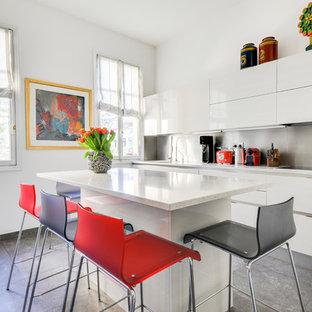 Cette photo montre une grande cuisine tendance avec des portes de placard blanches, un sol en carrelage de céramique, un îlot central, un sol gris, un placard à porte plane, une crédence métallisée et un plan de travail blanc.