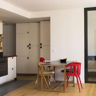 Aménagement d'une cuisine américaine contemporaine en L avec un placard à porte plane, des portes de placard blanches, une crédence beige, un électroménager noir, un sol en bois brun, aucun îlot, un sol marron et un plan de travail noir.