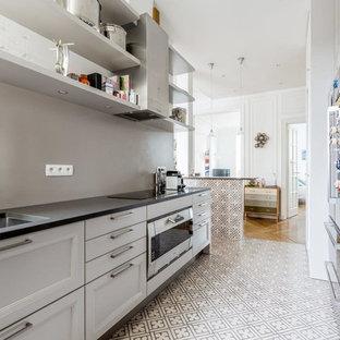 Cette photo montre une cuisine parallèle tendance fermée et de taille moyenne avec un évier encastré, des portes de placard blanches, une crédence grise, un électroménager encastrable, un sol en carrelage de céramique et aucun îlot.