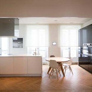 Aménagement d'une grande cuisine américaine contemporaine en L avec des portes de placard noires, un sol en bois brun et une péninsule.