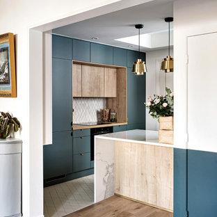 Идея дизайна: кухня-гостиная среднего размера в современном стиле с фасадами с декоративным кантом, синими фасадами, мраморной столешницей, серым фартуком, фартуком из терракотовой плитки, техникой под мебельный фасад, полом из терракотовой плитки, островом, белым полом и белой столешницей