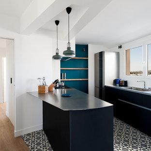 Aménagement d'une cuisine parallèle contemporaine avec un évier intégré, un placard à porte plane, des portes de placard noires, un plan de travail en inox, un électroménager en acier inoxydable, une péninsule et un sol multicolore.