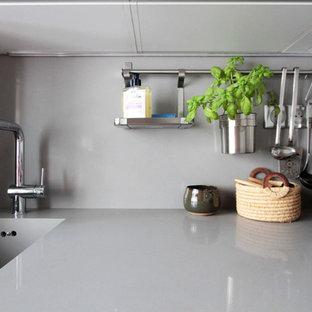 中サイズのエクレクティックスタイルのおしゃれなキッチン (一体型シンク、インセット扉のキャビネット、白いキャビネット、珪岩カウンター、グレーのキッチンパネル、パネルと同色の調理設備、セメントタイルの床、アイランドなし、黒い床) の写真