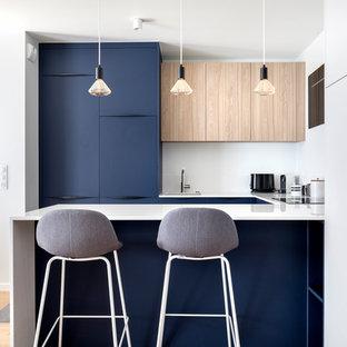 Idée de décoration pour une cuisine ouverte marine en U de taille moyenne avec un évier 1 bac, un placard à porte plane, des portes de placard bleues, un plan de travail en surface solide, une crédence blanche, un sol en bois clair, un plan de travail blanc, une péninsule et un sol beige.