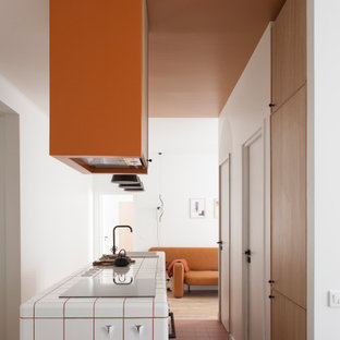 Mid-sized scandinavian single-wall open plan kitchen in Paris with an integrated sink, beaded inset cabinets, light wood cabinets, tile benchtops, grey splashback, panelled appliances, terra-cotta floors, with island, brown floor and white benchtop.