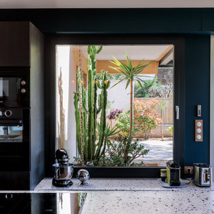 Photo of a mid-sized contemporary galley open plan kitchen in Marseille with an integrated sink, glass-front cabinets, black cabinets, terrazzo benchtops, black appliances, cement tiles, with island, blue floor and blue benchtop.