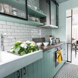 Einzeilige, Geschlossene, Mittelgroße Retro Küche ohne Insel mit Doppelwaschbecken, Glasfronten, Arbeitsplatte aus Holz, Küchenrückwand in Weiß, Rückwand aus Metrofliesen, Elektrogeräten mit Frontblende, Keramikboden und grünen Schränken in Paris