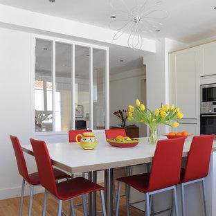 Idée de décoration pour une cuisine design en L fermée et de taille moyenne avec des portes de placard blanches, un sol en bois clair et un îlot central.