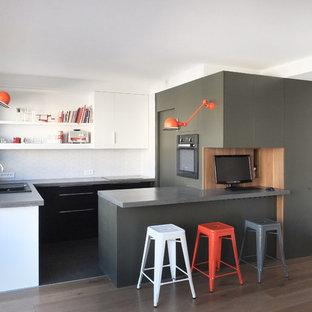 Immagine di una cucina minimal di medie dimensioni con ante lisce, paraspruzzi bianco, penisola, lavello da incasso, ante nere, top in cemento, paraspruzzi con piastrelle in ceramica e elettrodomestici da incasso
