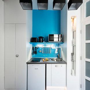 Aménagement d'une petit cuisine linéaire contemporaine fermée avec des portes de placard blanches et aucun îlot.