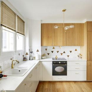 Idée de décoration pour une cuisine design en L de taille moyenne avec un évier posé, un placard à porte plane, des portes de placard blanches, une crédence multicolore, un électroménager encastrable, un sol en bois brun, un sol beige et un plan de travail blanc.