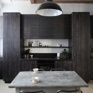 Idée de décoration pour une cuisine américaine linéaire design de taille moyenne avec une crédence noire.