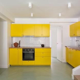 Mittelgroße Moderne Küche ohne Insel in U-Form mit Einbauwaschbecken, flächenbündigen Schrankfronten, gelben Schränken, Arbeitsplatte aus Holz, Küchenrückwand in Weiß, Rückwand aus Keramikfliesen, grünem Boden und beiger Arbeitsplatte in Paris