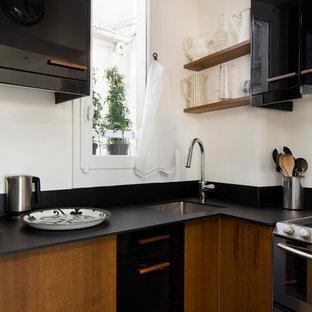 Inspiration pour une cuisine design en L avec un évier encastré, un placard à porte plane, des portes de placard noires et un plan de travail noir.