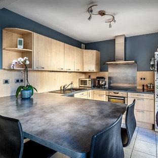 Cette image montre une cuisine américaine design en U de taille moyenne avec un évier 1 bac, des portes de placard en bois clair, une crédence métallisée, une crédence en dalle métallique, un électroménager en acier inoxydable, un sol en carrelage de céramique et une péninsule.