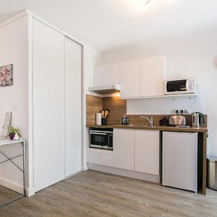 Idée de décoration pour une cuisine ouverte linéaire design avec un évier posé, un placard à porte plane, des portes de placard blanches, un plan de travail en bois, une crédence marron, une crédence en bois, un électroménager blanc, un sol en bois clair, aucun îlot et un sol beige.