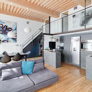 Inspiration pour une cuisine design en U avec un placard à porte plane, des portes de placard grises, un électroménager en acier inoxydable, un sol en bois brun, une péninsule, un sol marron, un plan de travail gris et un plafond en bois.