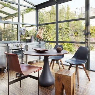 Exemple d'une grande cuisine américaine linéaire tendance avec un placard à porte plane, une façade en inox et un sol en bois foncé.